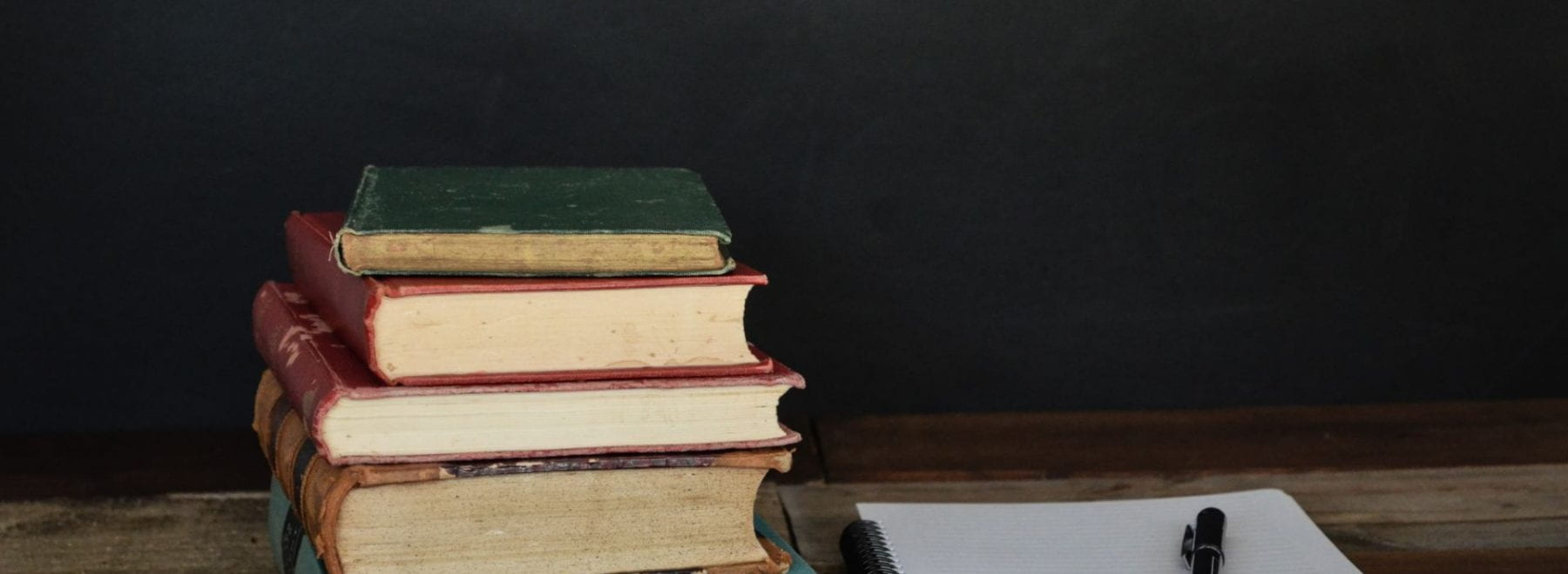 Stack of books on a desk next to an open notebook