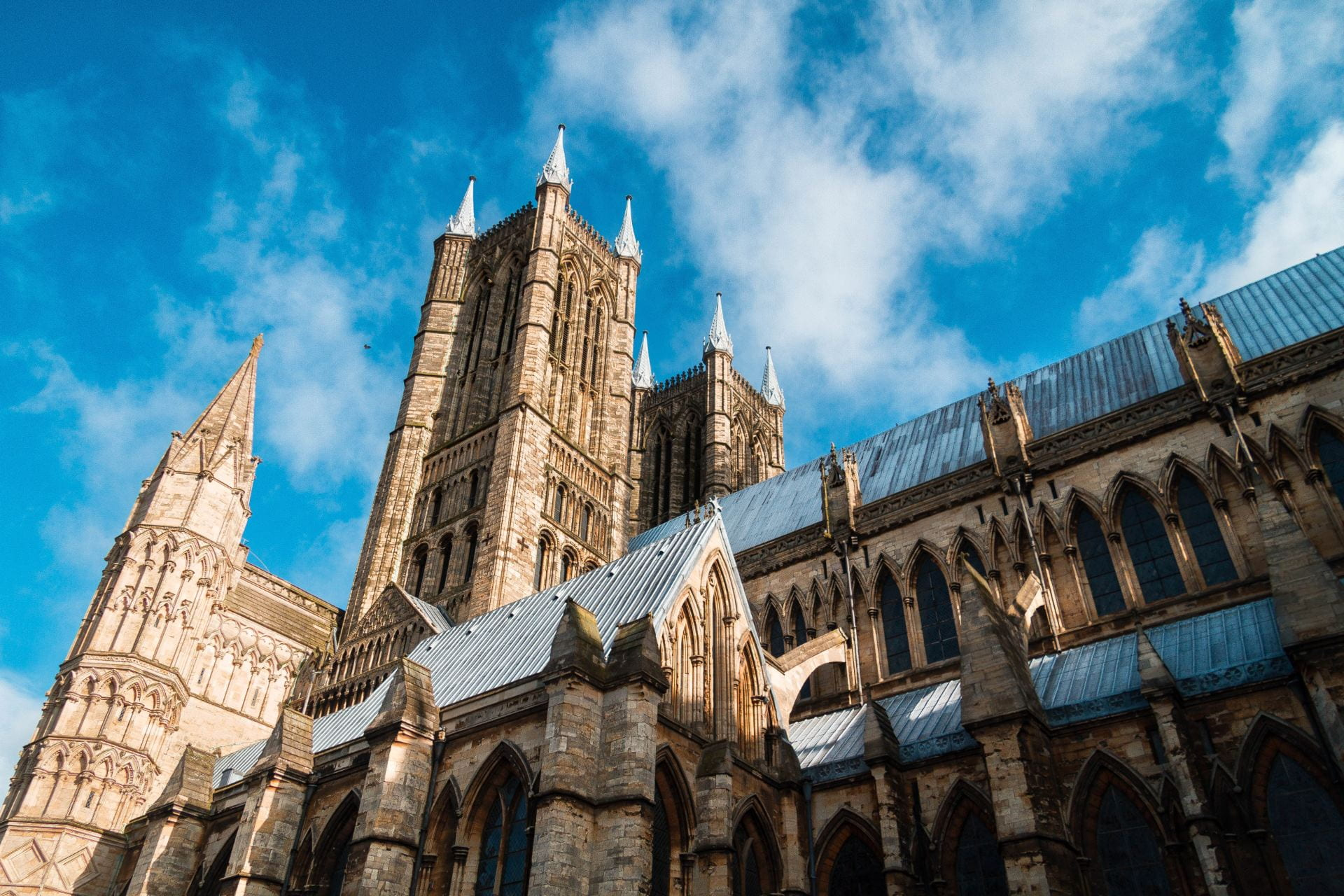 Lincoln cathedral, blue skies above it. With a few clouds in the sky.