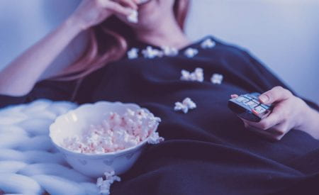 A girl smiling, eating popcorn