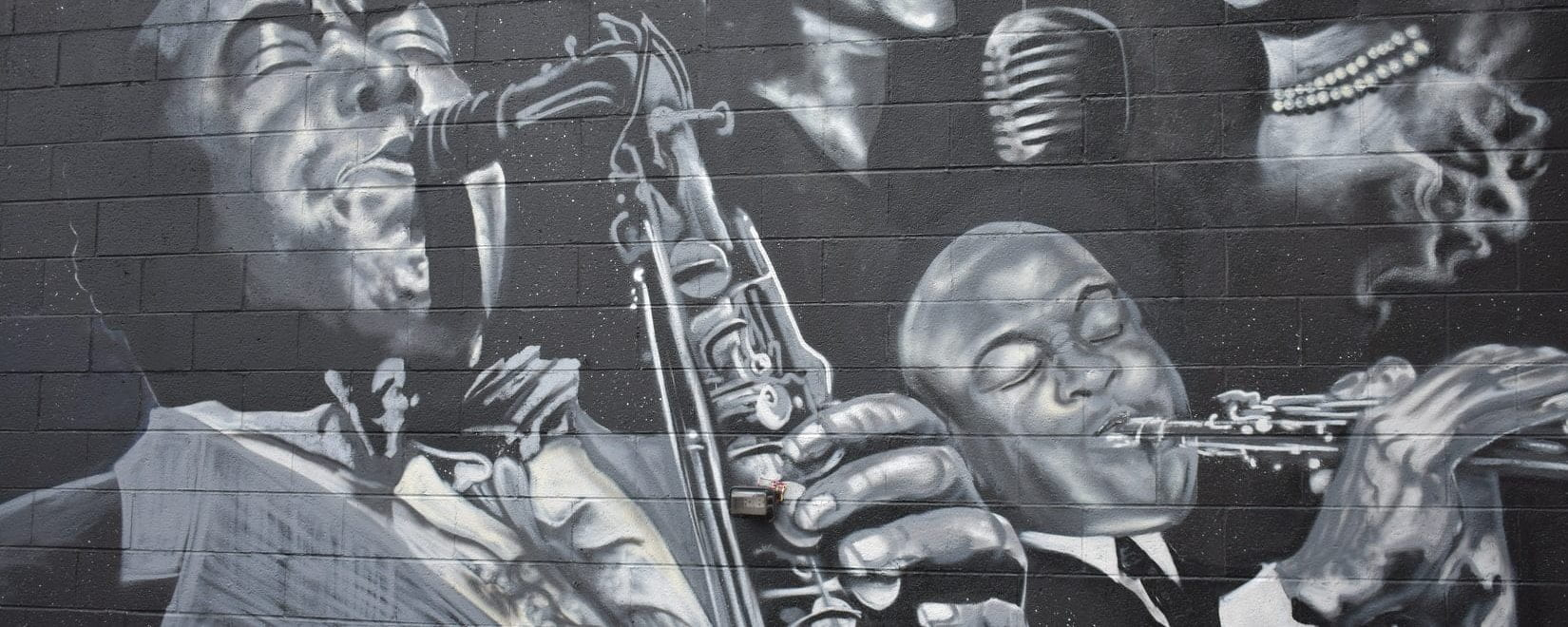 Black and white drawing on a wall of black musicians