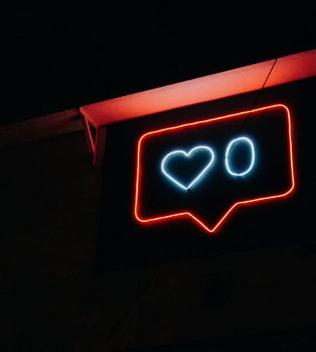 Neon sign of a pop-up with a heart and a 0.