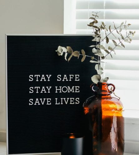 Framed photograph that reads: Stay Safe, Stay Home, Save Lives. Potted plant and a candle are in the foreground of the image.