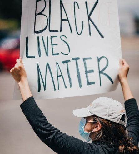 Girl with a hat on holding Black Lives Matter banner