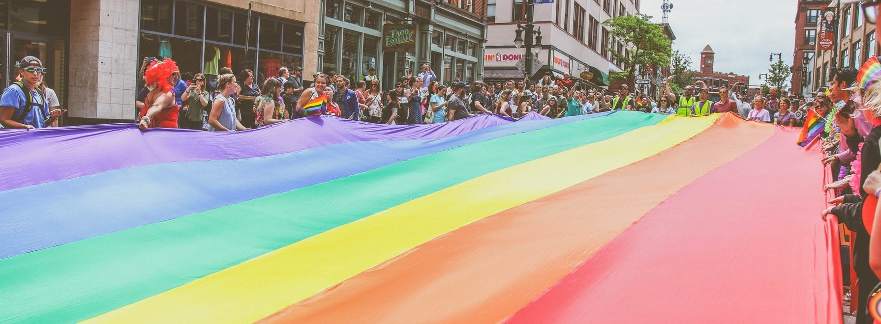 large rainbow flag being held by a large group of people in a city centre