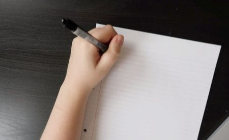 A person about to write on a piece of paper