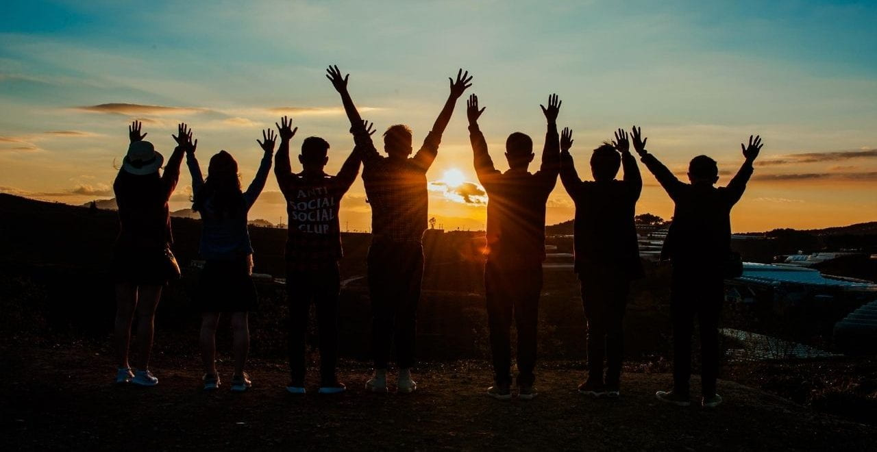 silhouettes of 7 people with their hands in the air watching the sunset