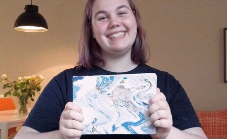 A girl smiling whilst holding a book