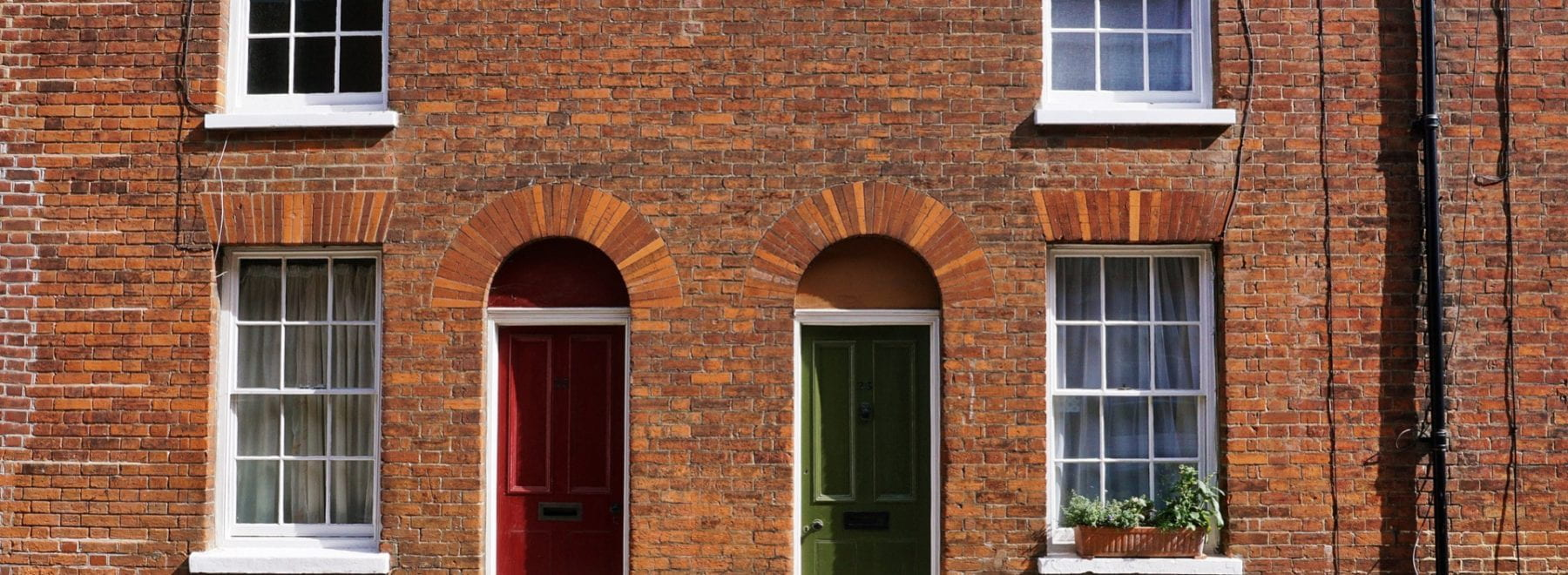 Front on photo of the exterior of a terraced house featuring a green and a red door