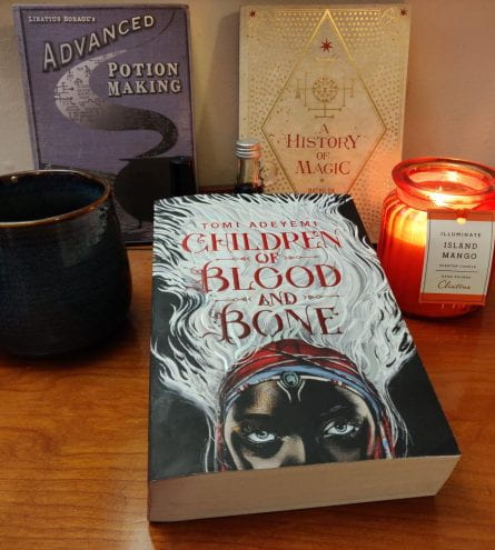 Focal book of 'Children of Blood and Bone' by Tomi Adeyemi next to a candle and a mug