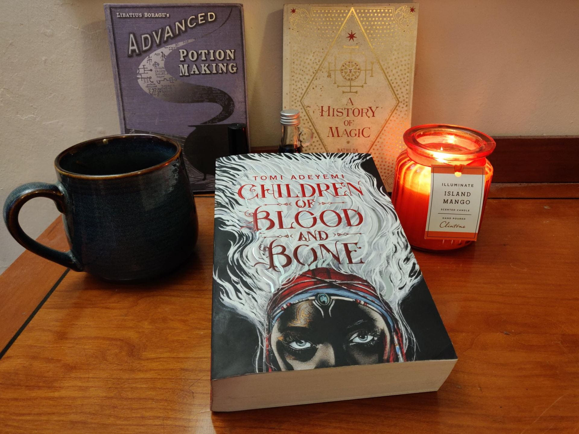 The book 'Children of Blood and Bone' with a candle and a mug