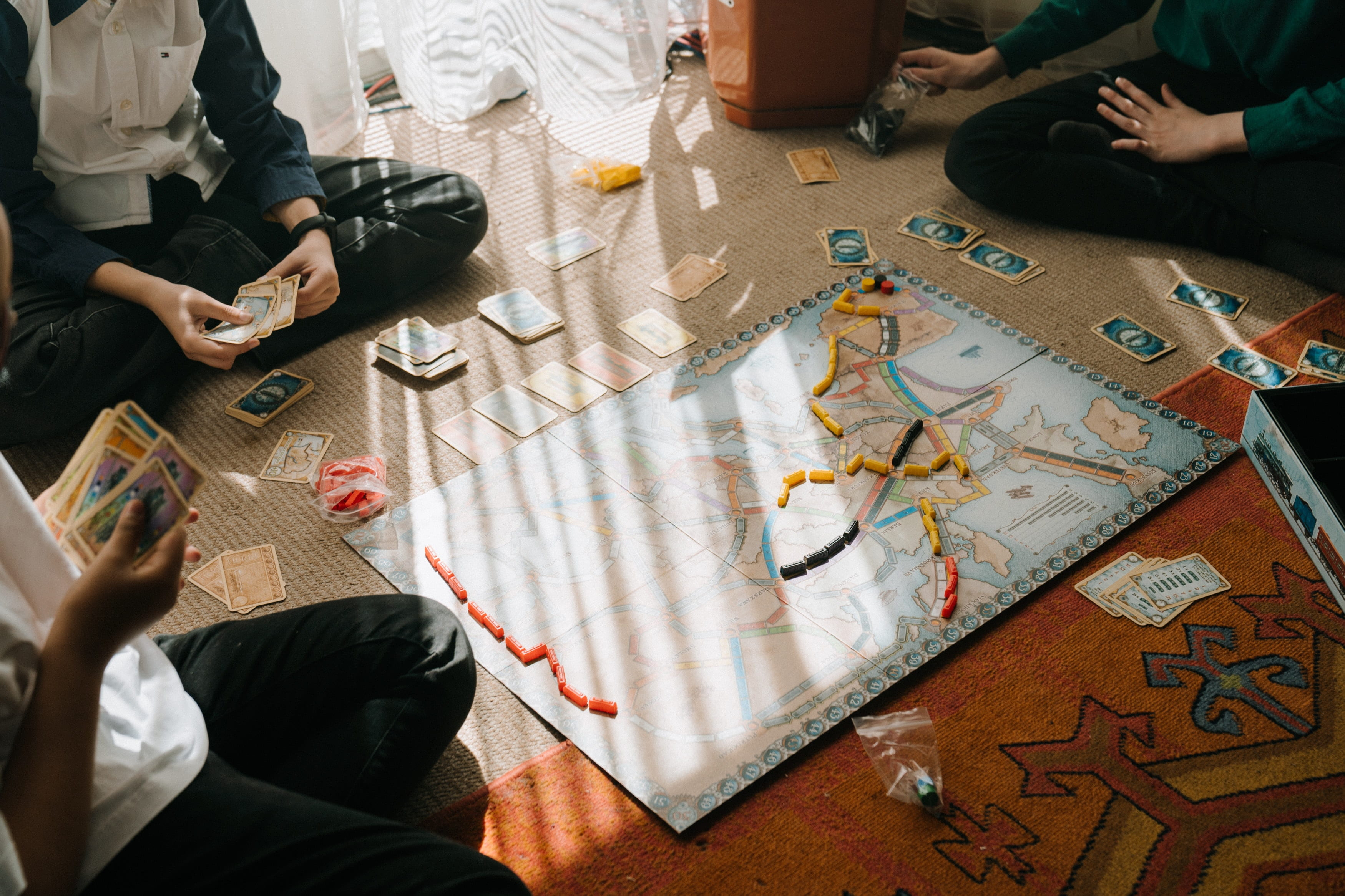 Group of people sitting on floor around a board game