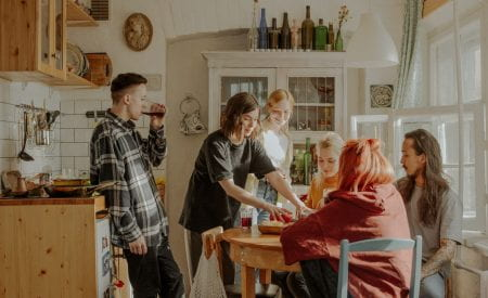Group of friends sat in a kitchen chatting to each other