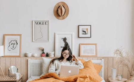 Girl sat in bed on laptop