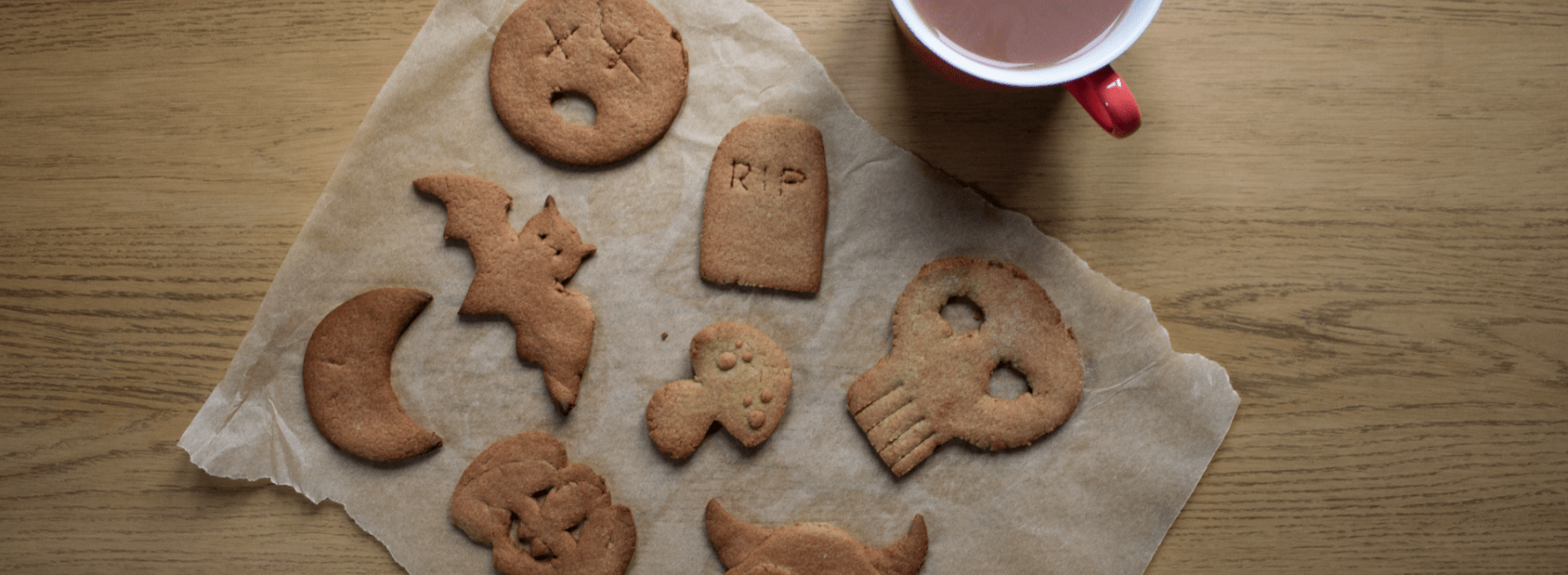 Flatlay showing handmade halloween biscuits sat next to a mug of tea