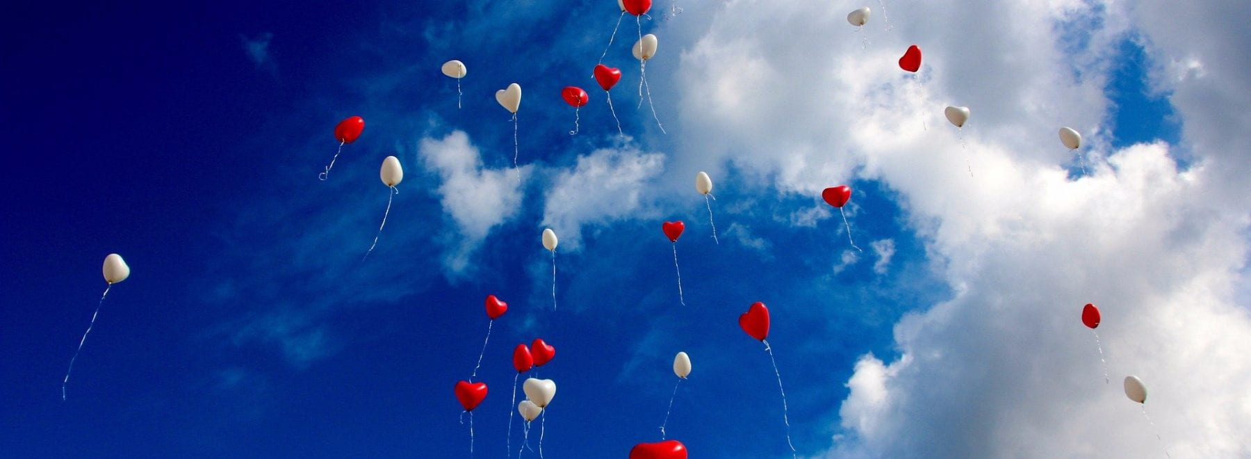 Heart shaped red and white balloons in the sky