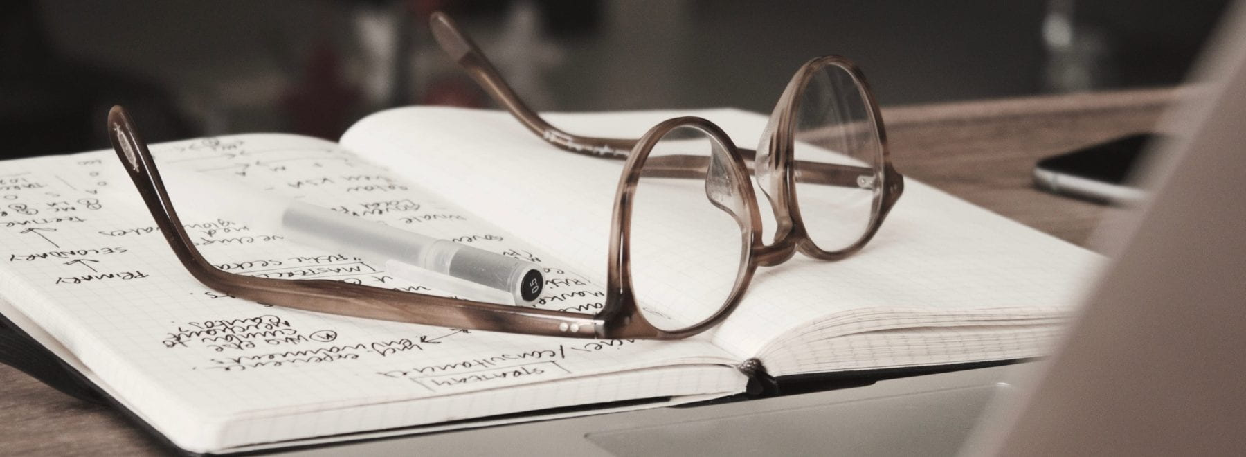 A laptop facing away with a notebook in front and glasses on top