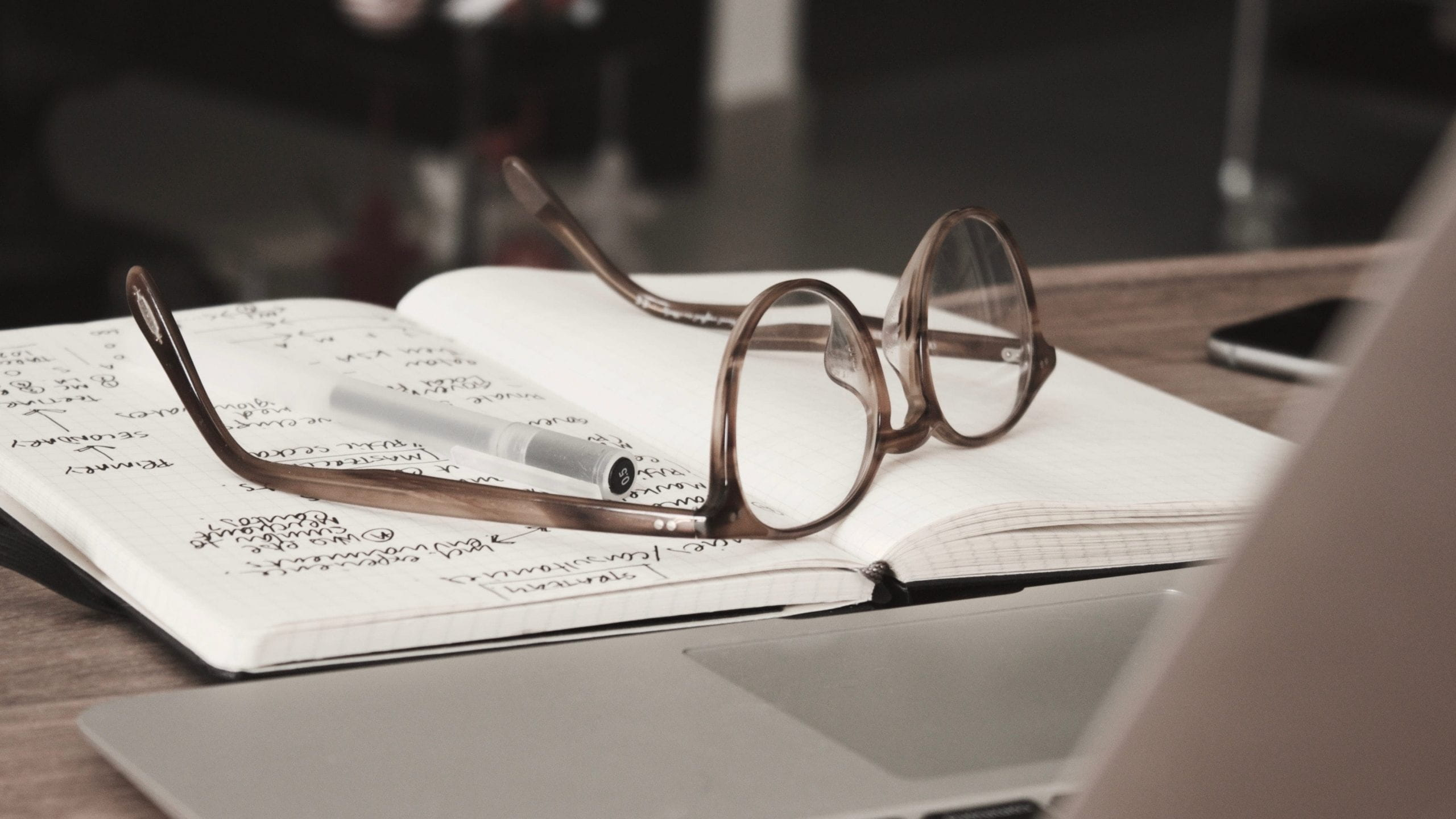 A pair of glasses on an notebook in front of a laptop
