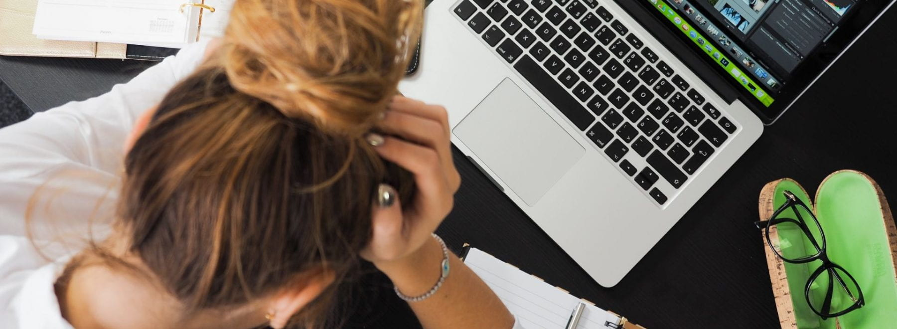 A woman stressed at her desk facing her laptop