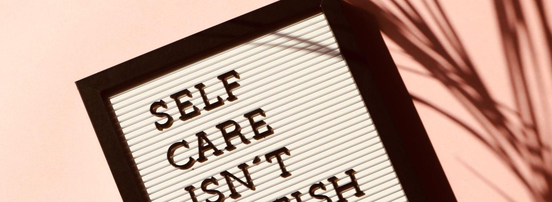 A board that reads 'self care isn't selfish'