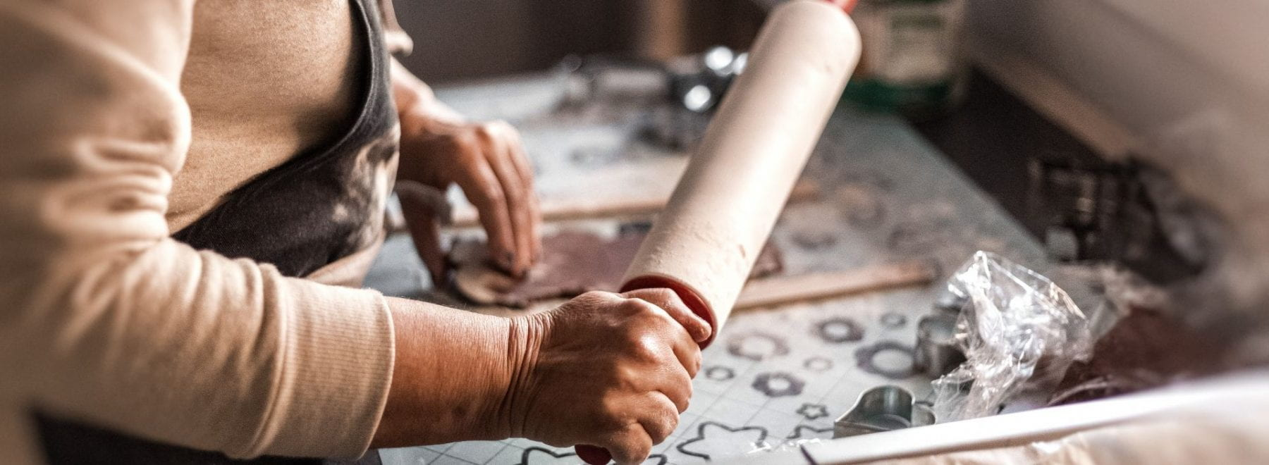 Close up shot of woman holding a rolling pin over a tray of dough
