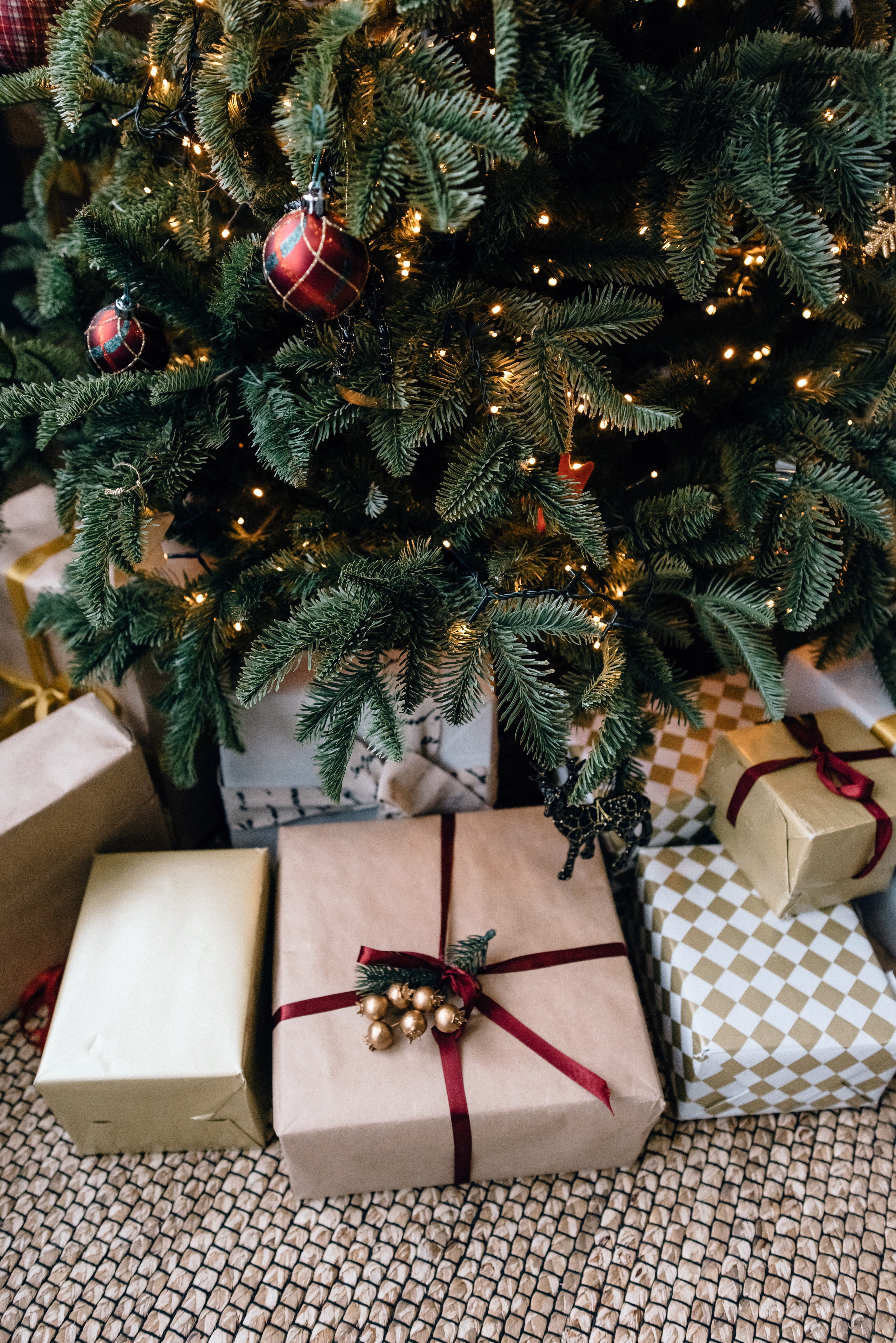 Close up of presents under a tree, wrapped in brown paper.