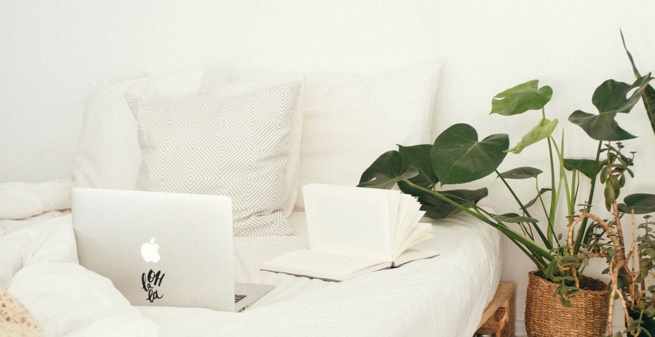 An organised white bed with a laptop and plants