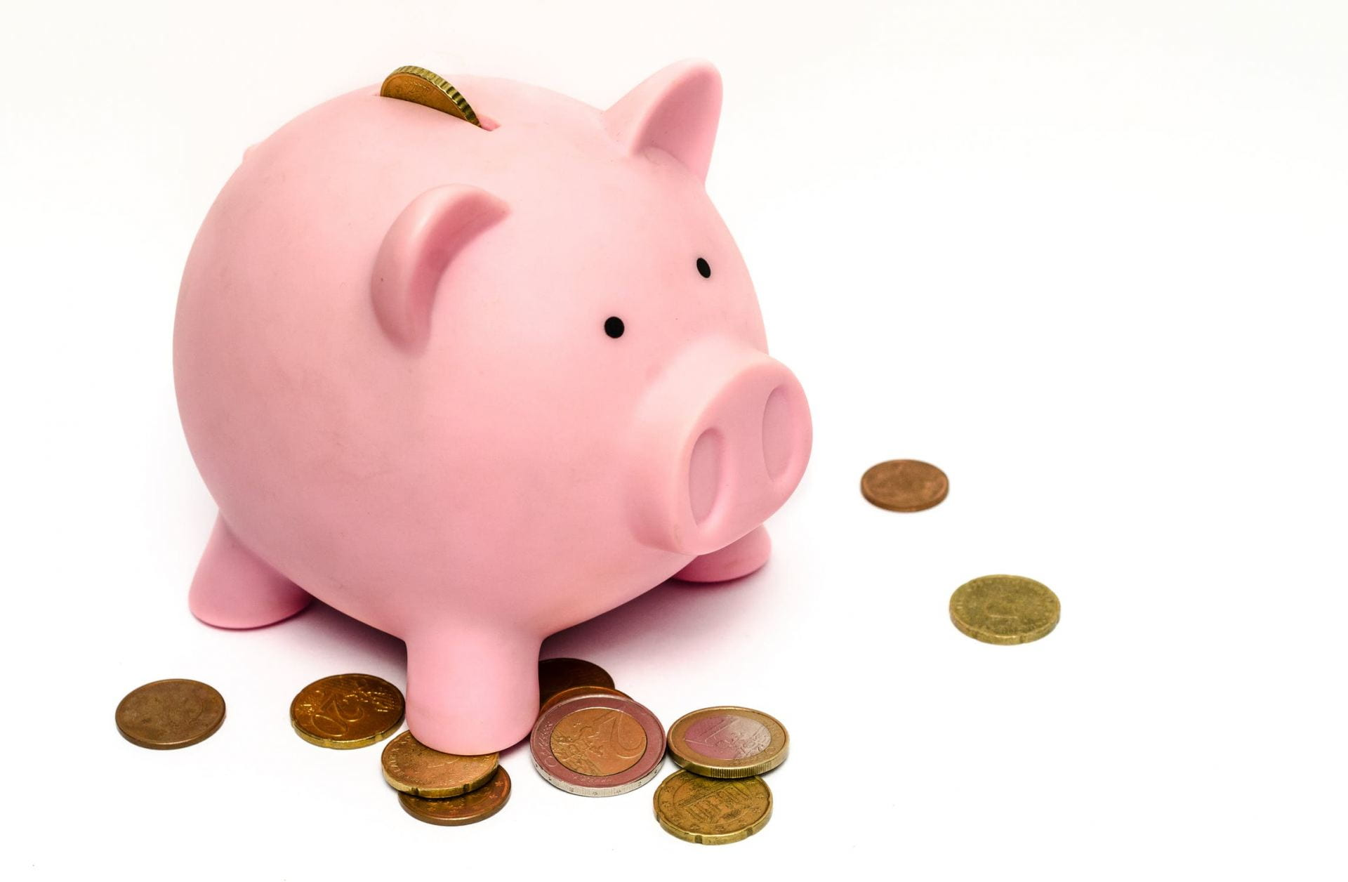 A pink piggy bank with a coin poking out. Around the bank are more coins.