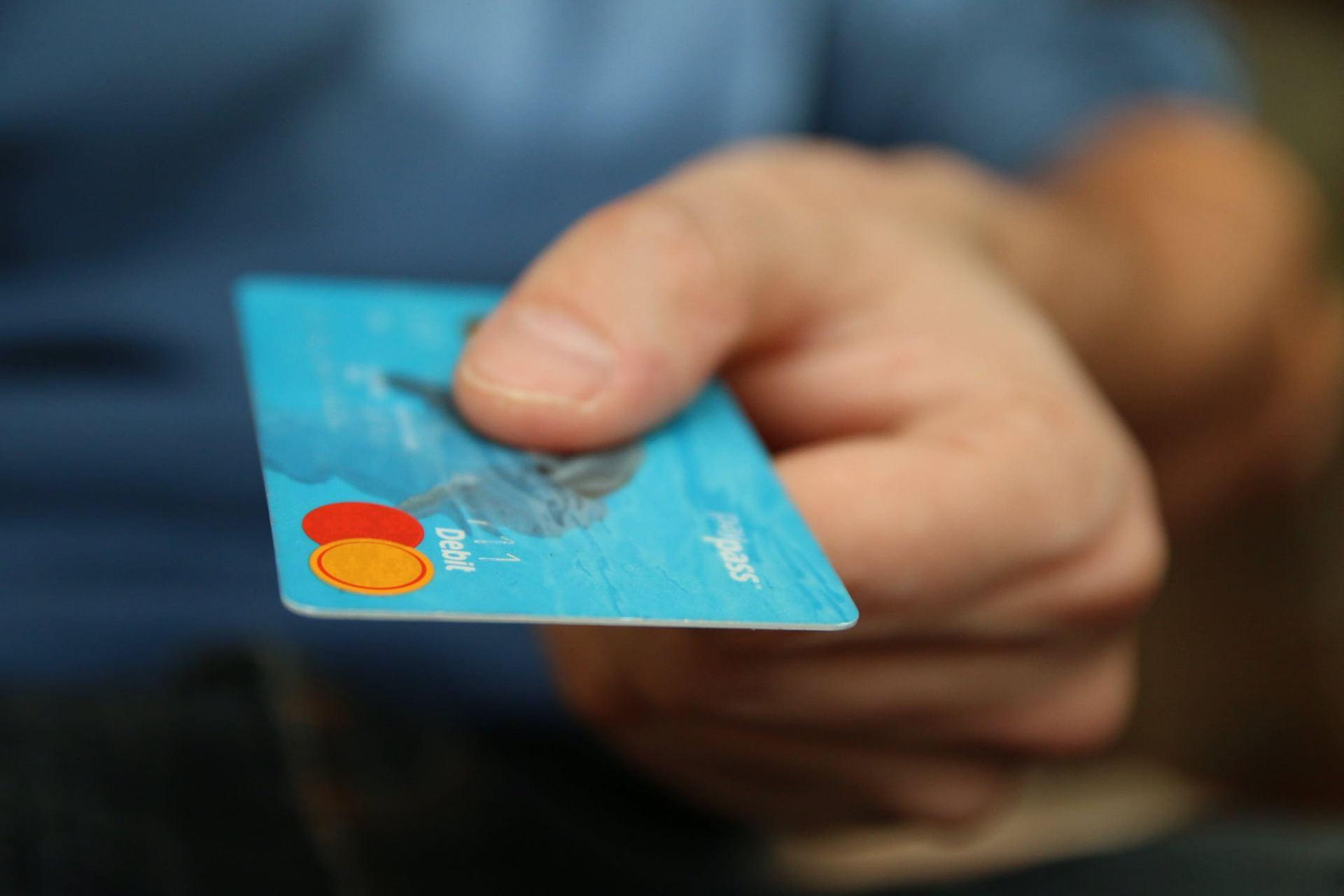 A hand holding a debit card forward.