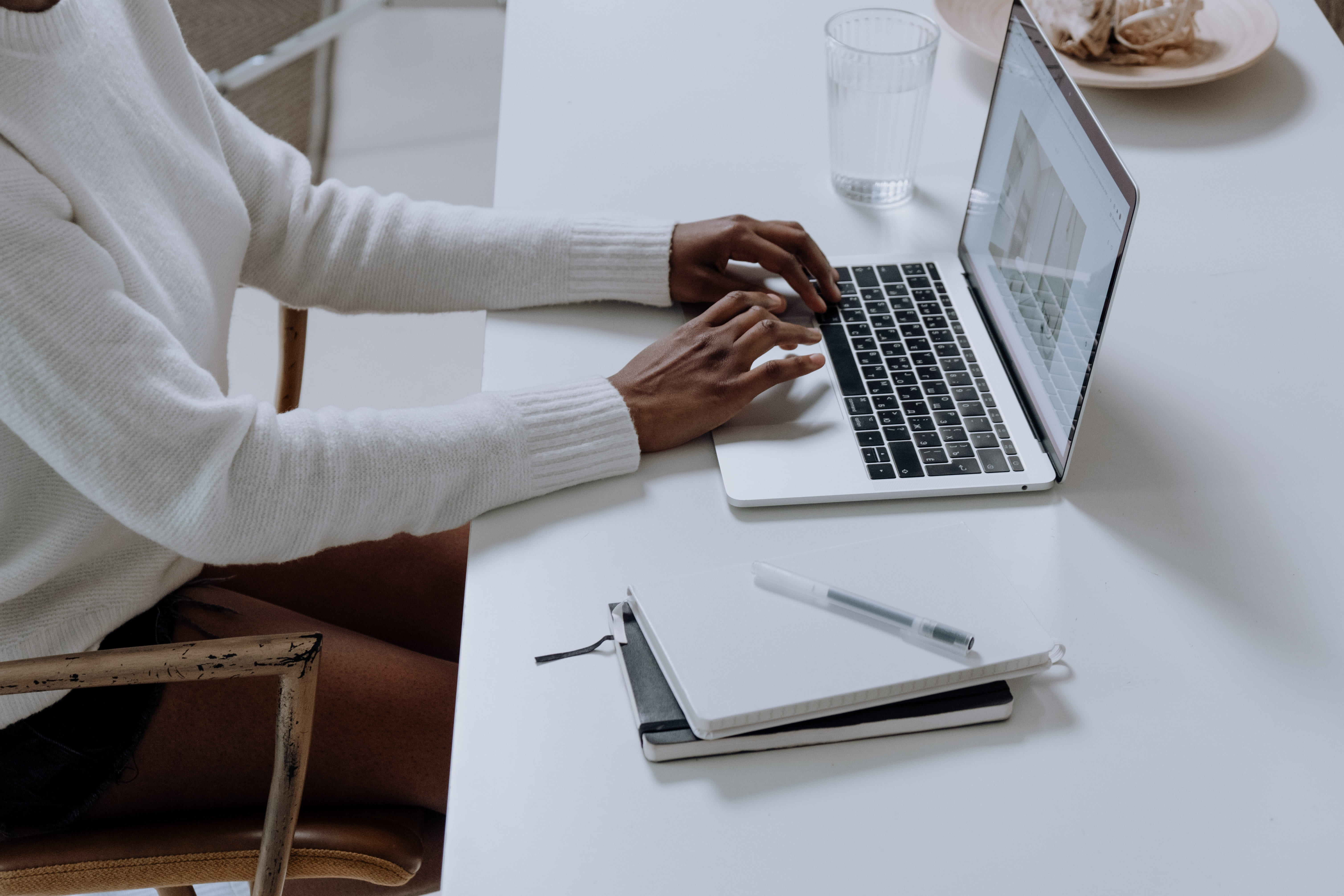 A person typing on a laptop sat at a desk. To their left is a glass of water and to their write are two notebooks and a pen.