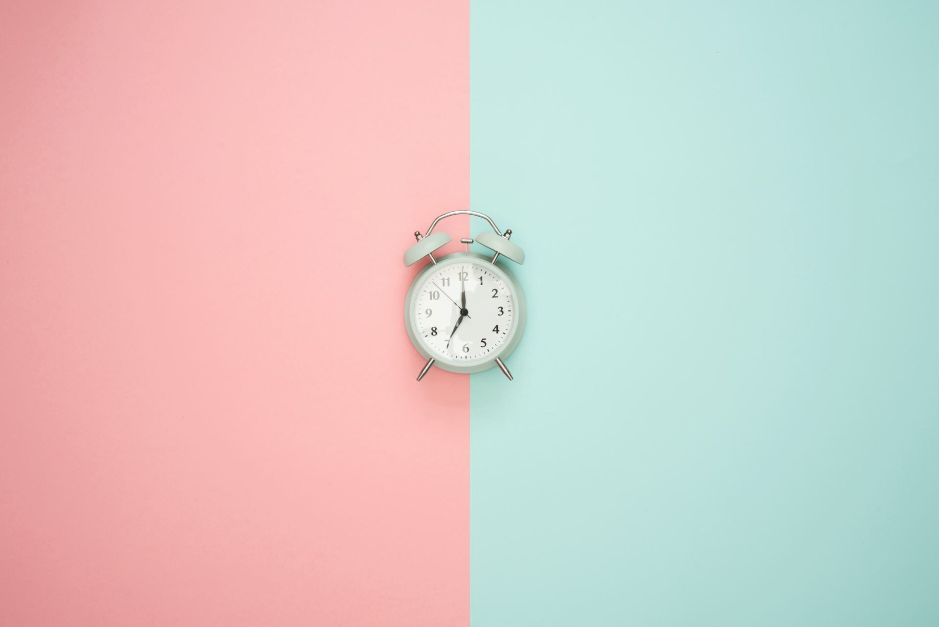An alarm clock in the middle of a background that is split exactly into two colours. The left is pink and the right is blue.