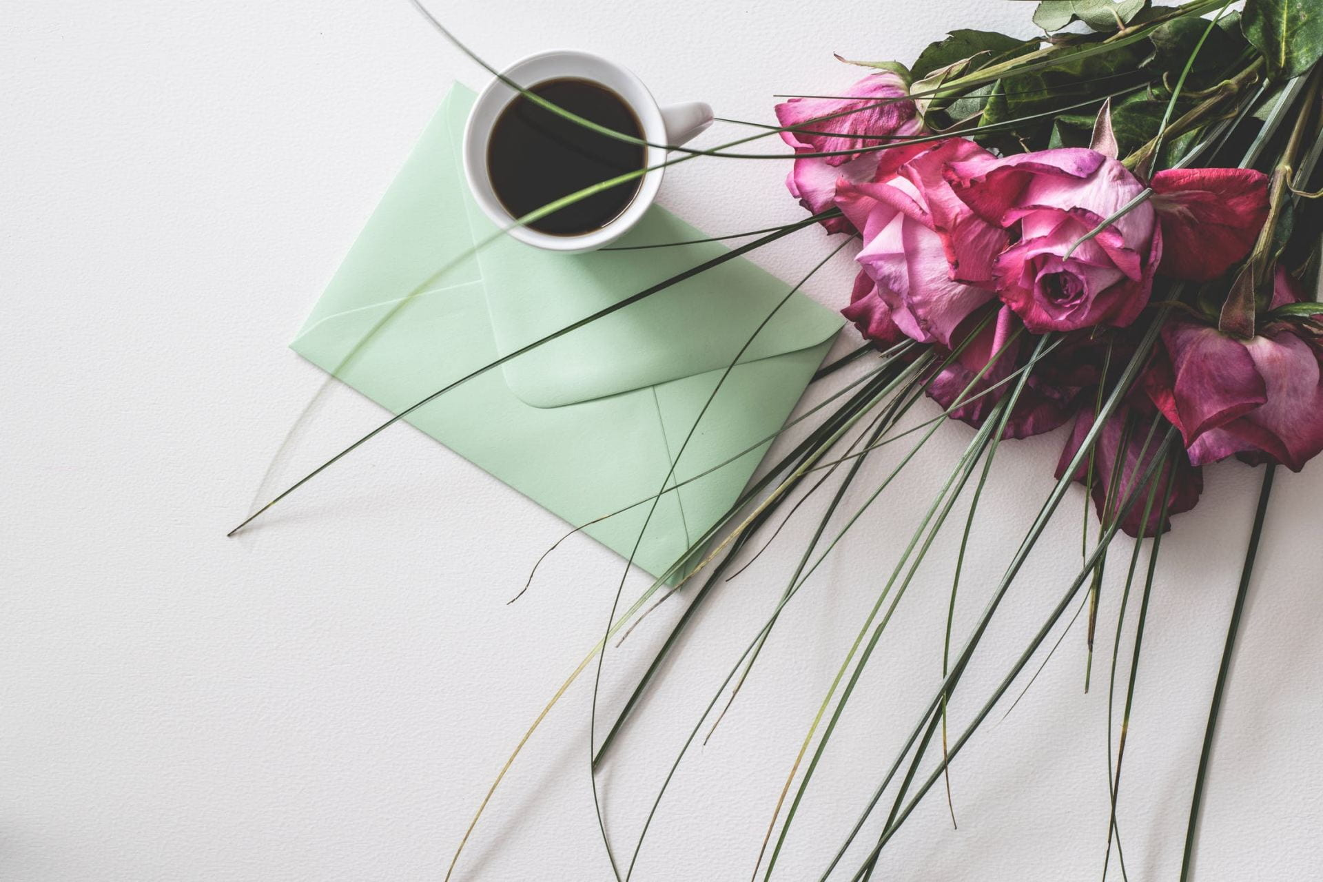 A green letter, a mug of coffee and a bouquet of pink roses on a white surface.