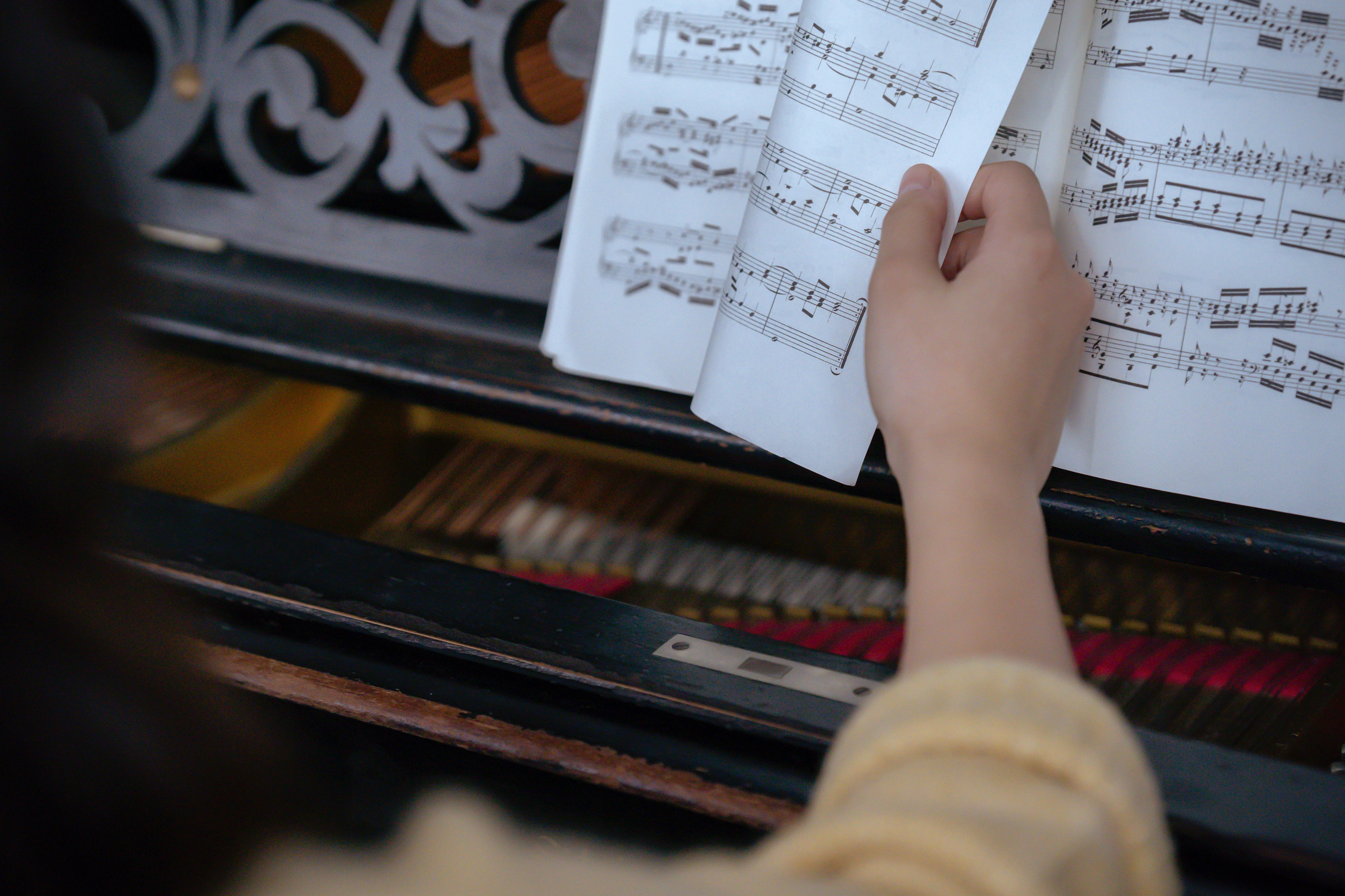 A hand turning the page of a book of music in front of a piano.