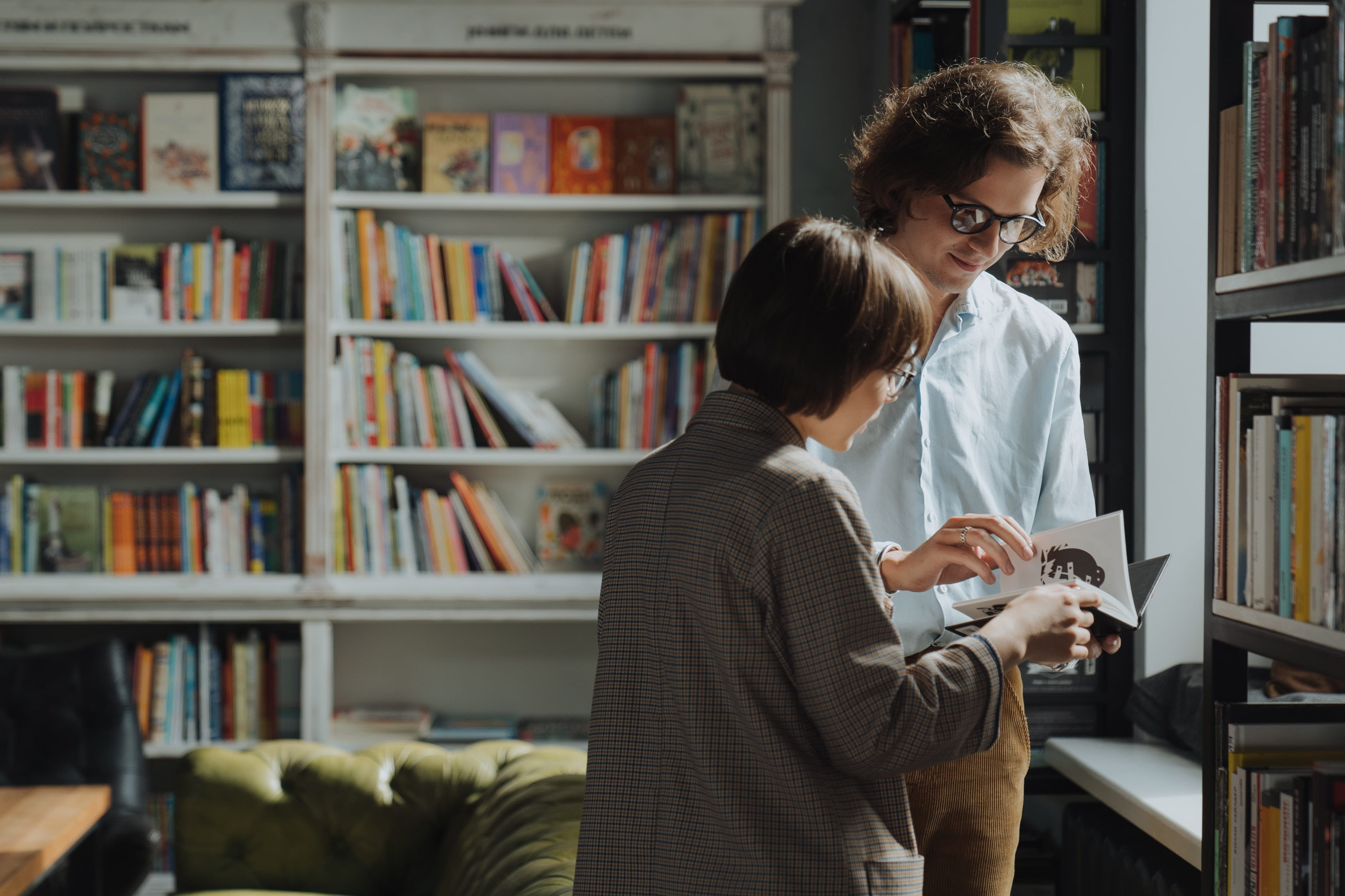 Two people surrounding by bookshelves both holding and looking at the same book. They both wear glasses on one is taller than the other.