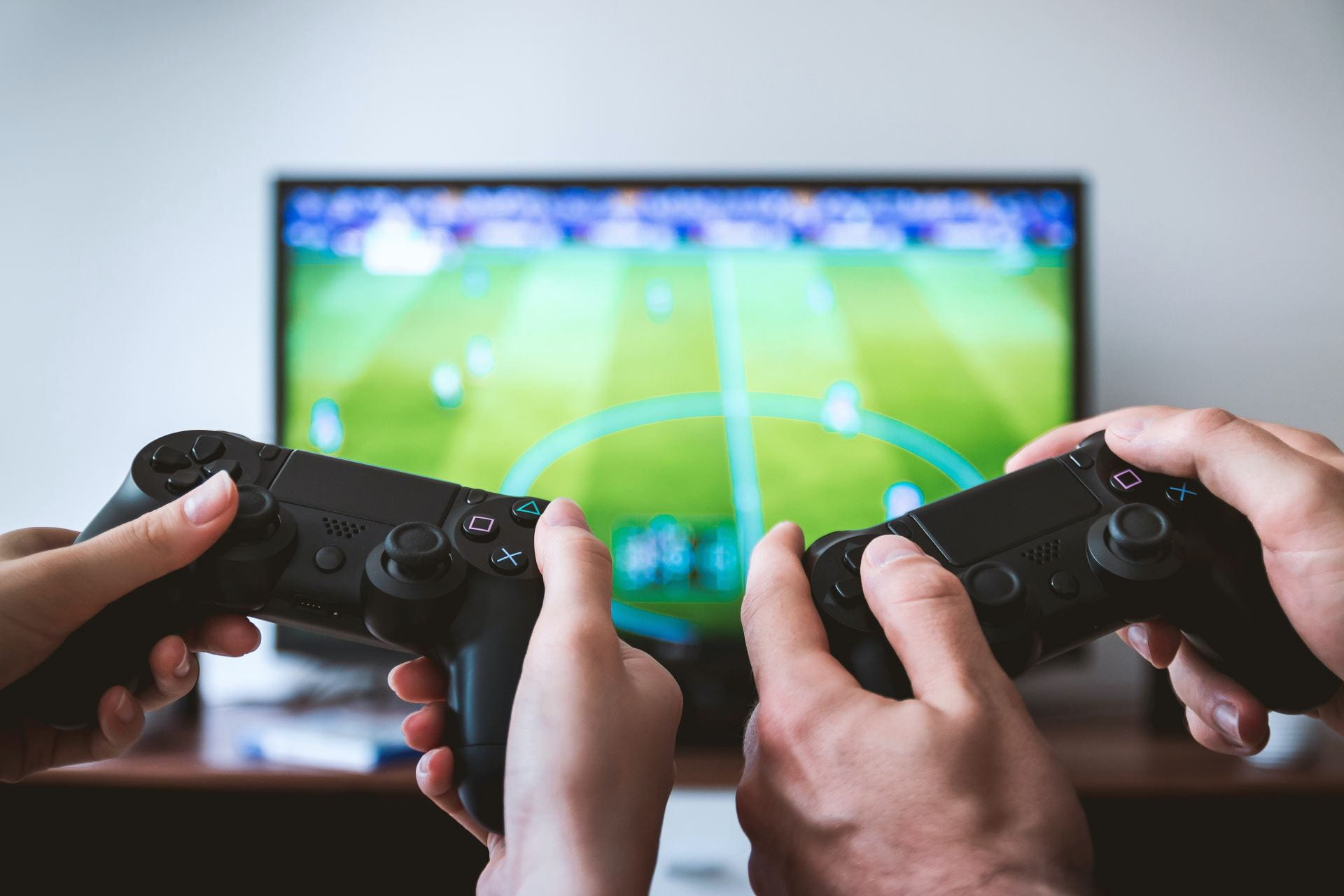 Two pairs of hands holding Playstation remotes. In the background there is a TV out-of-focus with a football game displayed.