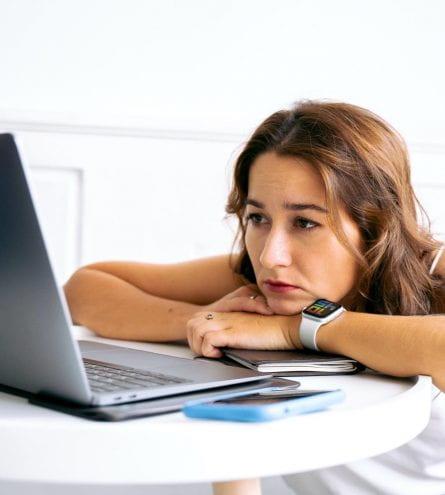 Someone sat facing their laptop slumped