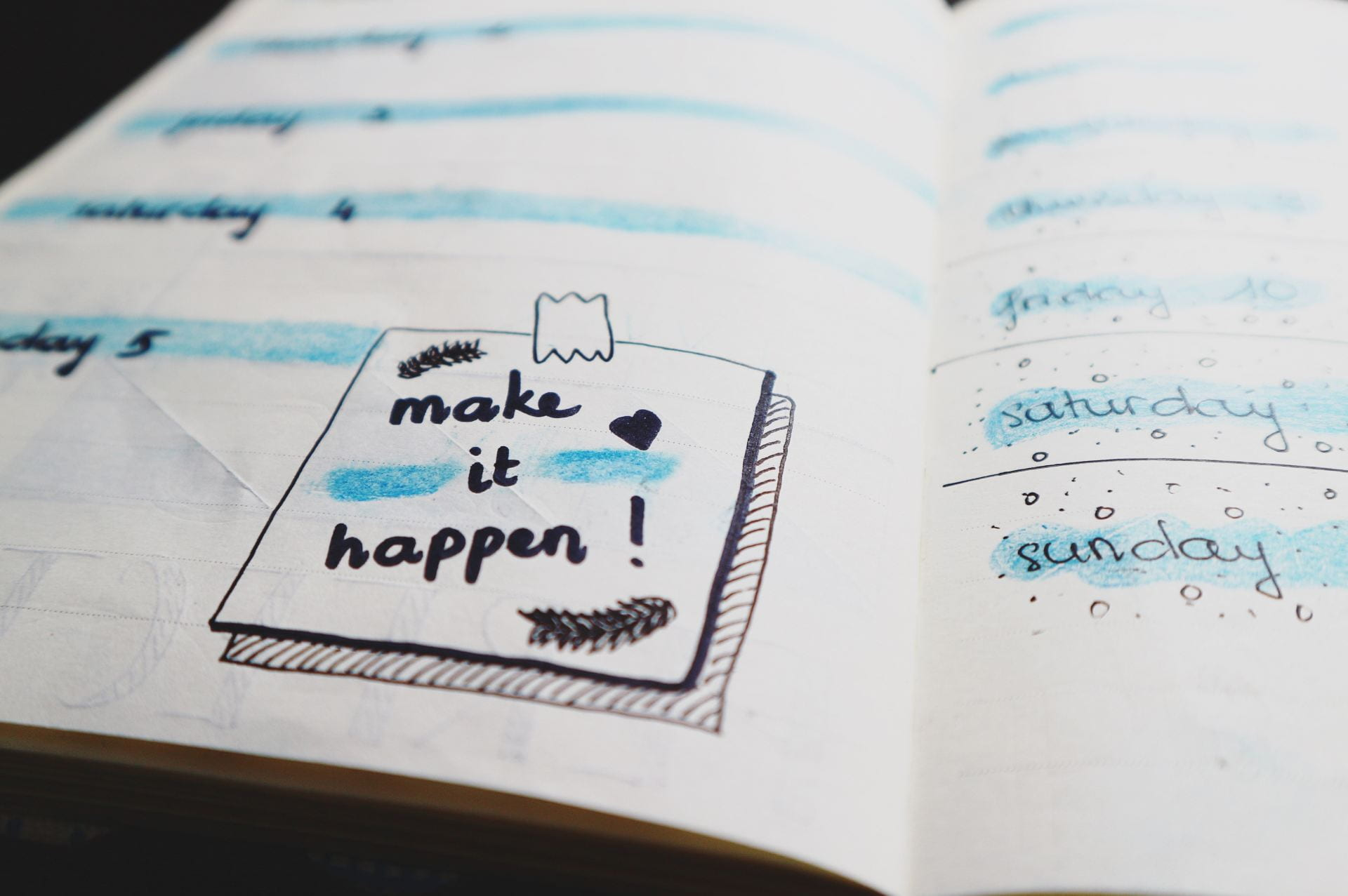 The inside of a planner. There is a drawing of a post-it note with the words 'Make It Happen!' on it.