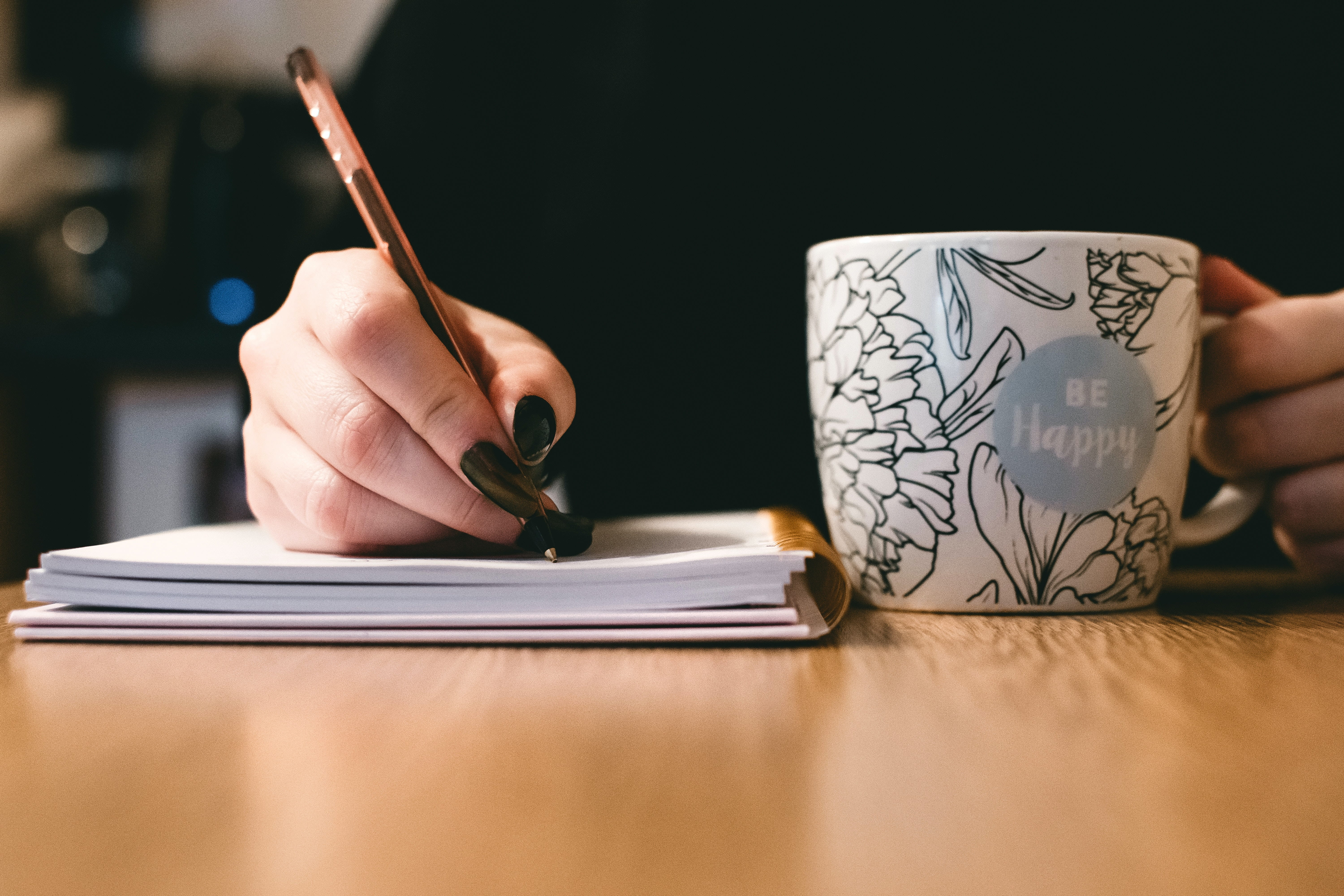 A hand writing in a notebook with a mug that says 'Be Happy' on it.