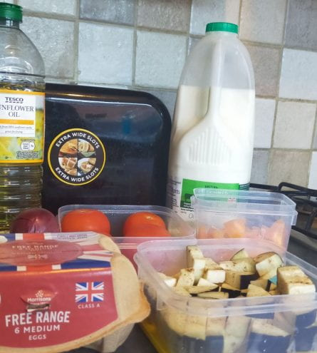 Cooking ingredients (milk, oil, tomato, onion, herbs, egg and aubergine)