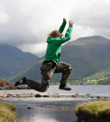 Someone jumping in the middle of a mountain and lake