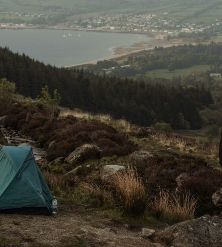 Tent up on the hills, with a man stood watching the view