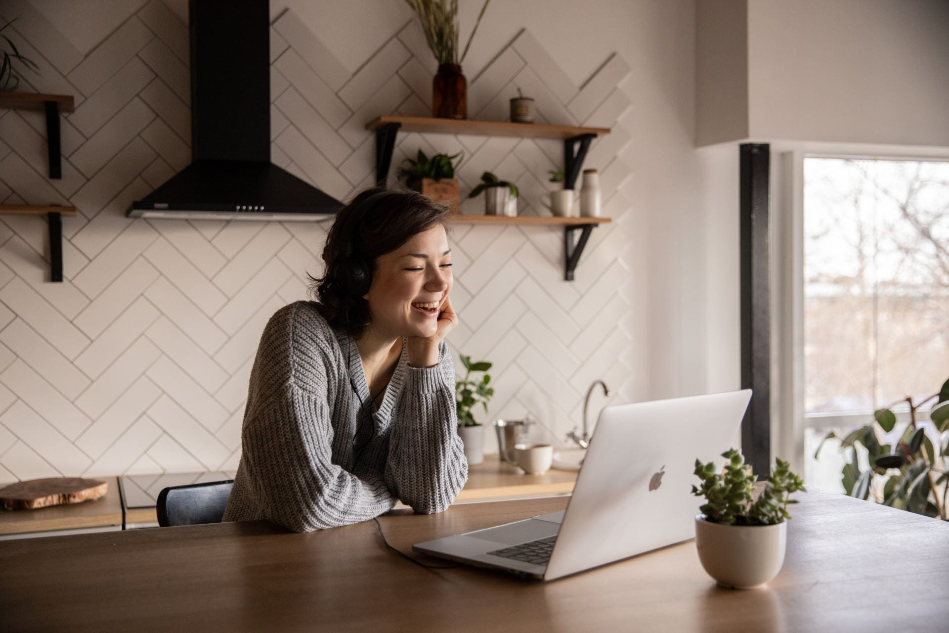 Woman laughing in front of a laptop