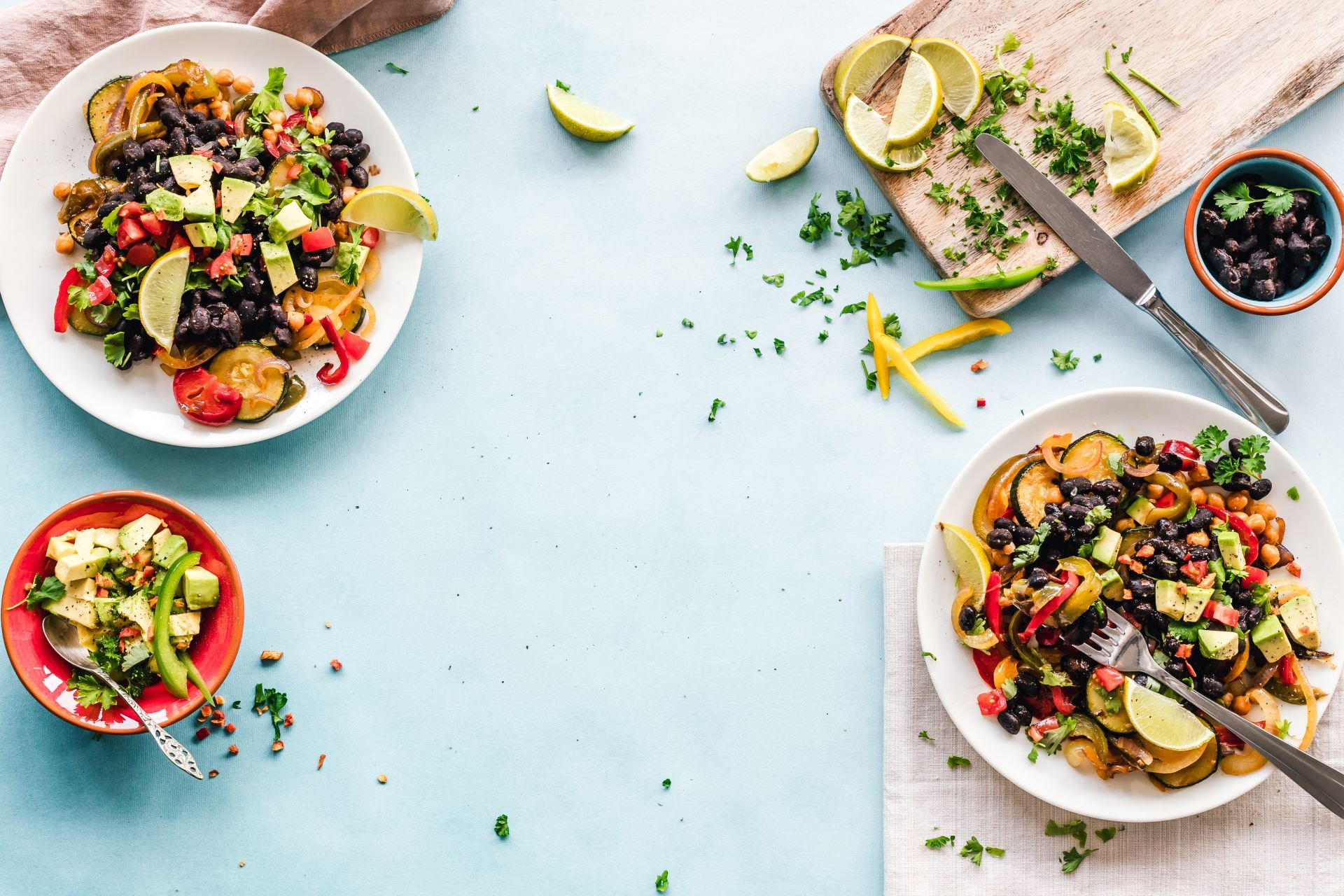 Three bowls of salad and a chopping board on a table.