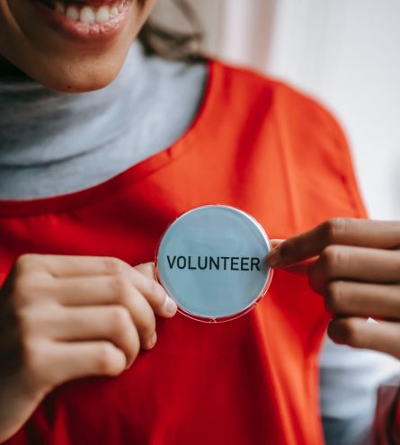 Someone putting on a volunteer badge