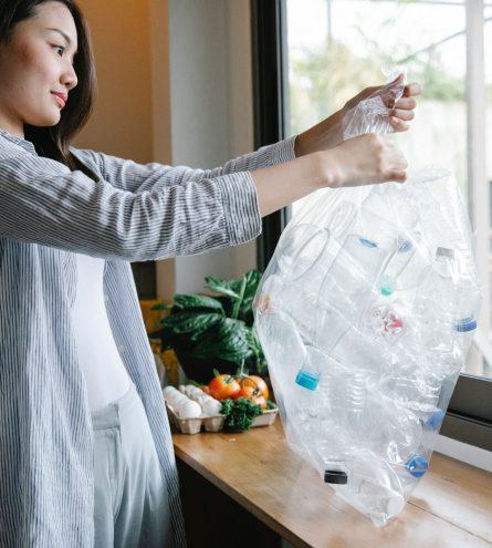 women holding bag of plastic bottles