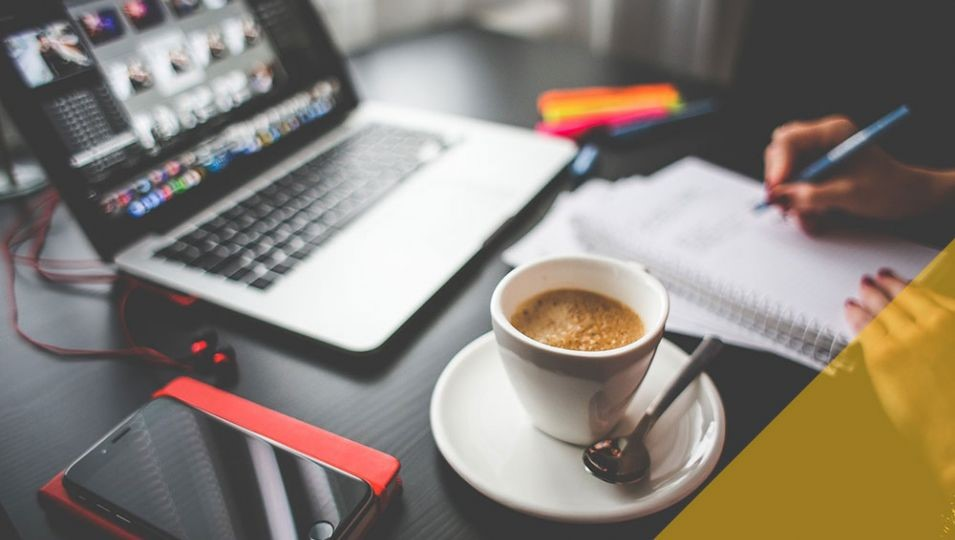 Person writing looking at their laptop with a coffee