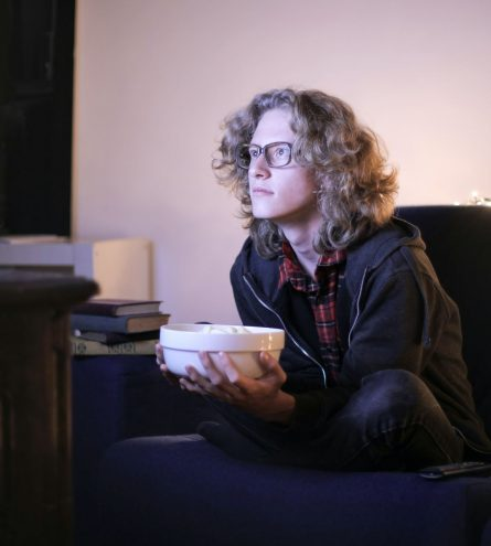 Someone watching TV with a bowl of food in their hands