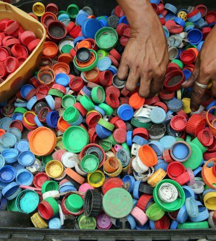 A tray full of hundreds of bottle tops