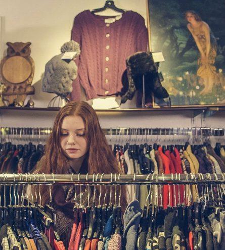 A woman browsing through a charity shop aisle