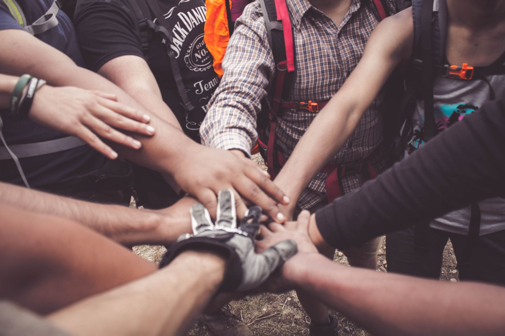A group of people all putting their hands together in the middle of a circle