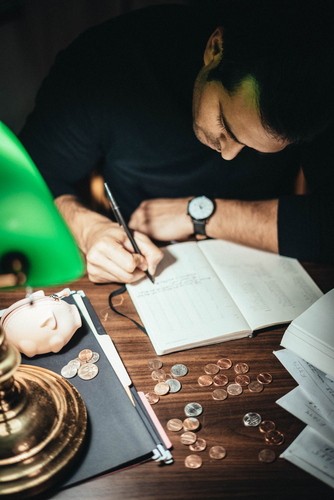 Man writing in a ledger. In front of him are coins and a piggy bank.